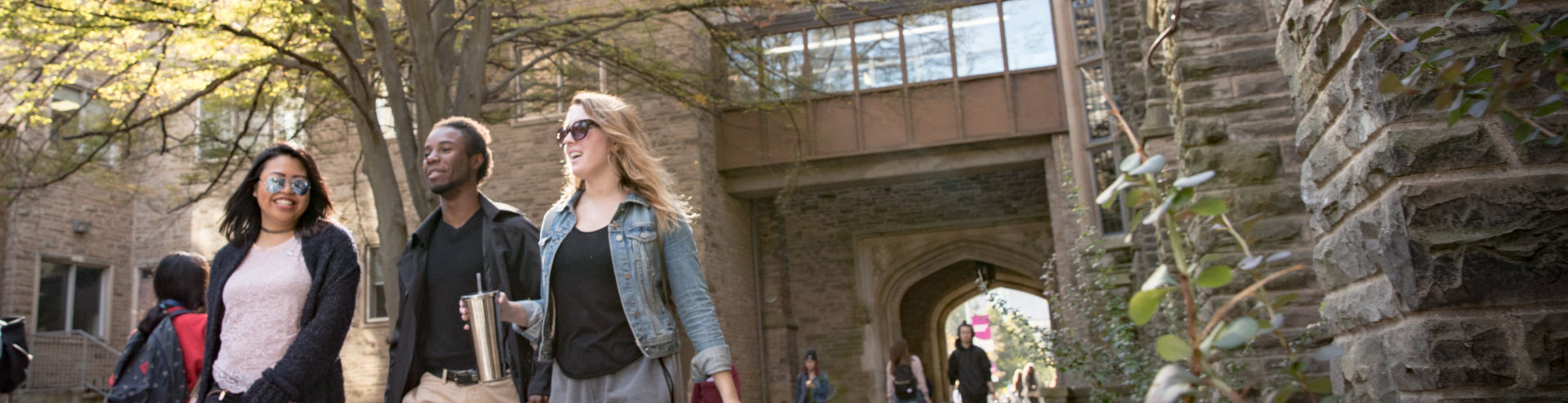 Three students walk on the pathway behind University Hall on McMaster campus